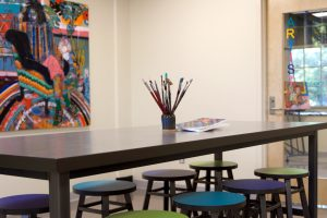 a gray table surrounded by blue and green stools. there is a jar with paintbrushes and a few canvases on top of the table. A colorful painting of an armchair hangs on the wall.
