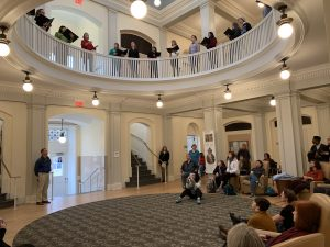 the rotunda of Hill Hall. A white room with a round opening in the ceiling. Singers perform from the balcony with an audience below.