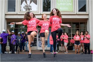 Three girls tap dancing on stage