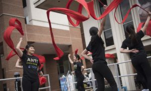 students dance on stage waving red ribbon