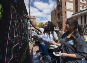 Students write with chalk on a chalkboard that has the Arts Everywhere logo on it.