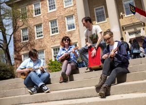 Four student sit on the steps of the South Building. Three of them each have their own ukuleles and are playing them. One is playing a box drum.