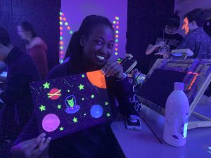 A student shows her space-themed painting which utilized glow in the dark paint