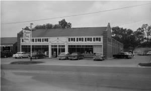 """A storefront with many windows and a sign that reads """"Fowlers Food Store."""" Many cars are parked in front and along the side of the building. black and white"""
