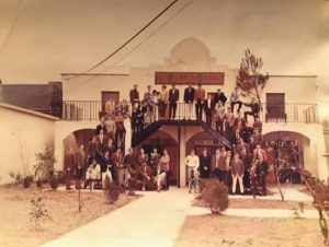 Sepia tone photo of a large group of people standing outside on the stairs of He's Not