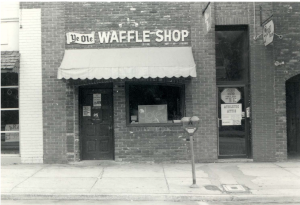 black and white image of Ye Olde Waffle Shop. It is a brick building with an awning over a door and window