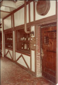 shelves of alcohol next to a wooden door. there is a sepia effect on the image