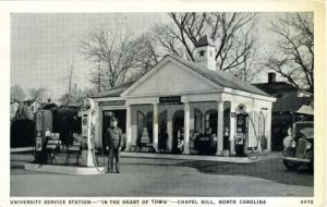 a small white building with columns and gas pumps. a gas attendant stands in front of one of the pumps. in black in white