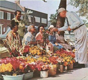 Six ladies standing and sitting in front of buckets of flowers. one of them is exchanging a bouquet for money from a man