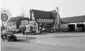 """black and white. There are two garages on the right with cars. There is a drive through area in the center with two cars and a gas pump. The overhead part has a sign that reads """"DeSoto Plymouth."""" On the street, there is a jeep with a sign that reads """"Poe Motor Company"""""""