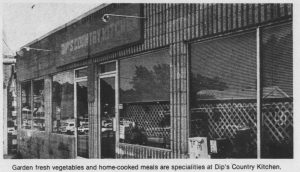 """Storefront with sign that reads """" Dip's Country Kitchen."""" The caption reads """"Garden fresh vegetables and home-cooked meals are specialties at Dip's Country Kitchen."""""""