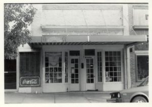 storefront with an awning. There is a Coca Cola sign in one of the windows. black and white