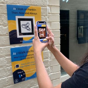 a white brick wall has an Art Walk marker. The marker is blue and yellow with a cartoon rat on it. Two arms are holding a phone to scan the marker.