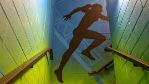 blue and green background with black silhouette of female runner