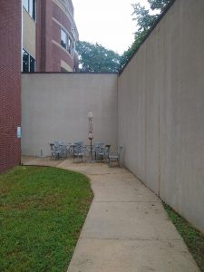 Close up of walkway leading to wall with chairs and table at the corner